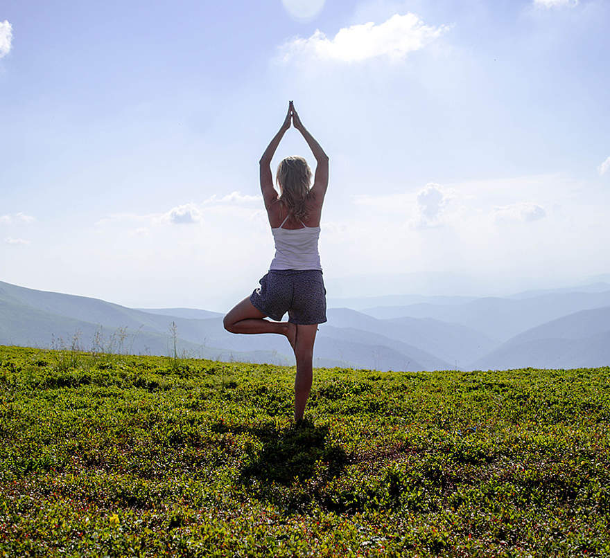 Yoga (Woman meditating in tree yoga position on the top of a mountains at daylight | 301005509) © (Marina Linchevska | www.shutterstock.com)